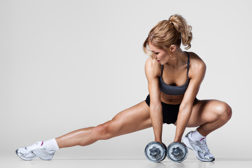 athletic woman pumping up muscles with dumbbells and stretching legs-img-blog